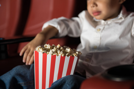 Closeup of a little boy sitting in a movie theater and enjoying a movie while eating popcorn