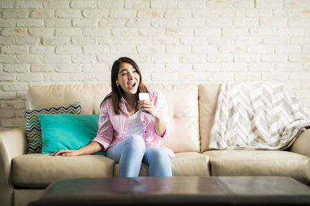 Hispanic woman having fun singing her favorite song while she spends a relaxing afternoon at home Stock Photo
