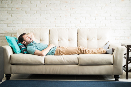 Stock Photo   Young Adult Man In A Casual Outfit Lying Down In A Cozy Sofa  In The Living Room Doing Some Meditation