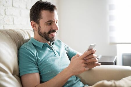 sms: Attractive man having fun online texting with his friends using his phone at home with a big smile Stock Photo