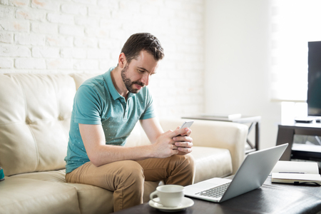 sms: Latin man smiling and texting with his phone while he works at home and drinks some coffee Stock Photo