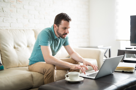独立した男が自分のコンピュータで自宅で働いているとリビングルームでコーヒーのカップを飲みます