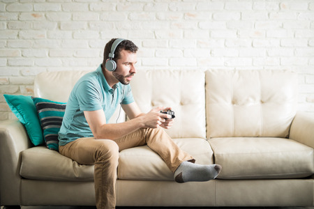 Attractive man concentrated in playing video games at home for entertainment while he is alone