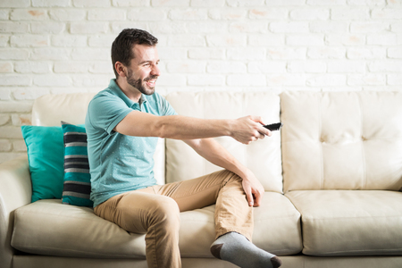 Hispanic man in his 30s wearing casual clothes and having fun alone at home watching movies