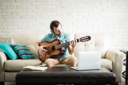 Creative young Latin man composing a new song and recording it into the computer