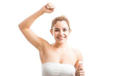 Gelukkige jonge vrouw die haar arm opheft en haar haar vrije oksels toont na het scheeren met een scheermes