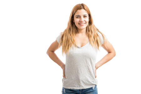 Portrait of a beautiful young woman with her arms in her waist and smiling in a studio Stok Fotoğraf
