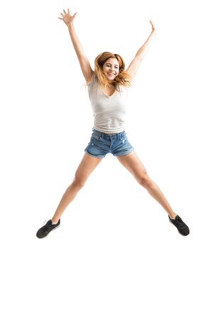 Carefree woman looking happy and excited while jumping with her arms and legs extended 免版税图像