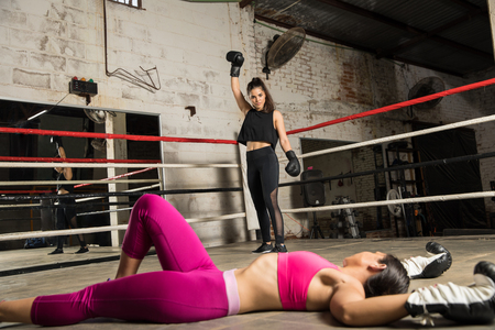 Good looking young woman looking at her defeated opponent after knocking her out on a box fight in a boxing gym