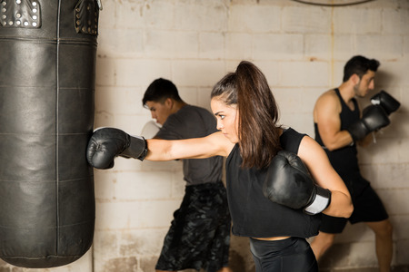 Profile view of a beautiful female boxer using a punching bag to train next to a group of people in a gym