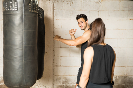 Good looking young man giving some technique advice to a woman in a boxing gym