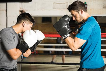 Deux boxeurs masculins sur le point de se battre sur un match inégal dans un ring de boxe Banque d'images