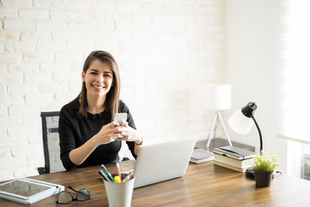 Beautiful Hispanic woman using her smartphone for texting and social media at the office