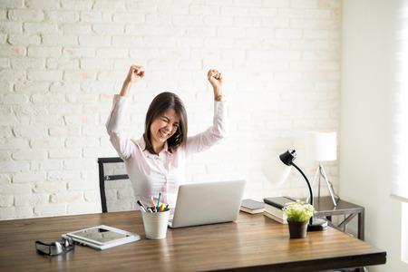Opgewekte vrouw die de computer met behulp van en wat goed nieuws viert met haar omhoog wapens