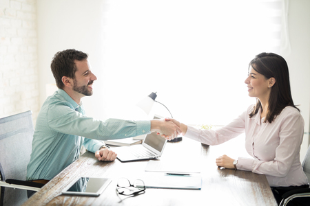 Attractive business man closing a deal with a woman by shaking hands and signing a contract Zdjęcie Seryjne