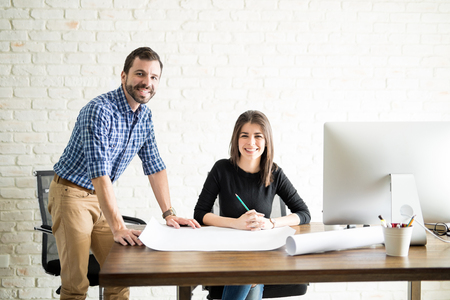 architectural firm: Happy architects working together on a project at the office and drawing some building plans