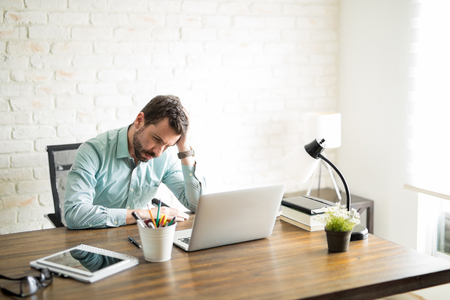 Frustrated independent business owner sitting with a hand on his head and a worried look