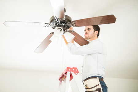 Portrait of a busy handyman standing on a ladder and fixing a ceiling fan in a house