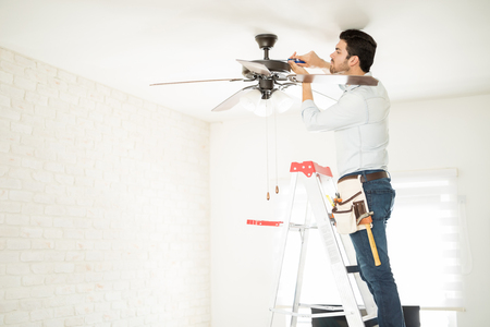 Profile view of a male electrician stepping on a ladder and installing a ceiling fan in a house Stock fotó