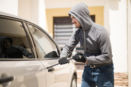 Profile view of a burglar wearing a hoodie and forcing a car door with a plank Stock Photo