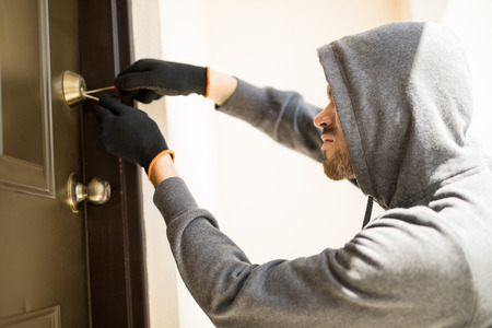 Profile view of a man with a hoodie trying to pick a lock in a house and forcing his entry Reklamní fotografie