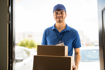 Hispanic young delivery man bringing some packages to a house and smiling Standard-Bild