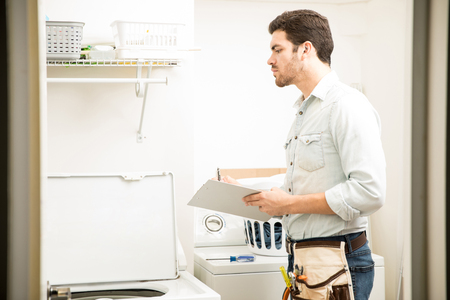 Profile view of a young male technician fixing a washing machine and writing a report Stock Photo