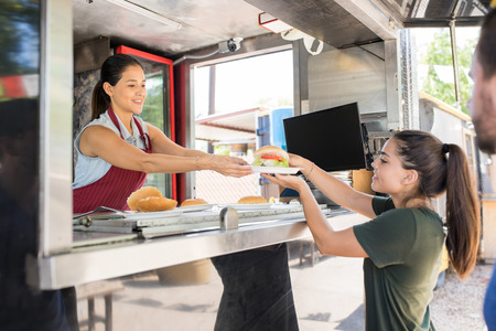 Profile view of a food truck worker handing over a hamburger to a customer and smiling