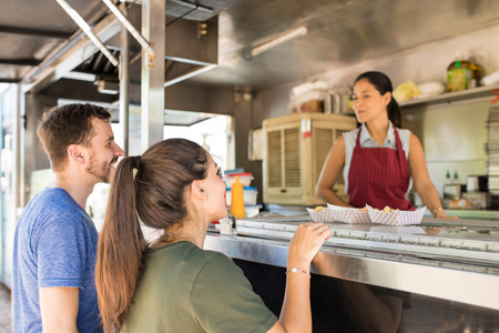 Profile view of a couple of customers lining up in front of a food truck and buying some food