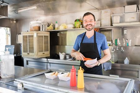 음식을 스탠드에서 일부 핫도그를 준비 하 고 웃 고 좋은 찾고 히스패닉 남자의 초상화