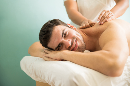 Handsome young man lying on a massage bed and getting pampered in a health spa and smiling