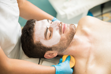 Portrait of a good looking relaxed man getting a facial treatment and looking very happy