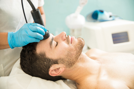 Profile view of a good looking young man getting a RF facial treatment in a health spa Banco de Imagens