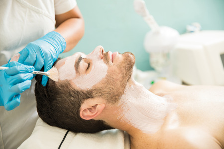 Profile view of a young man getting a moisturizing facial treatment in a health spa