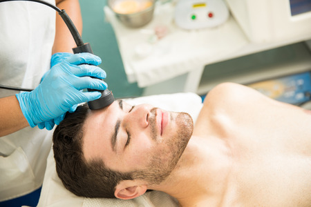 Relaxed Hispanic young man getting cellular and rejuvenation facial therapy in a spa Stockfoto