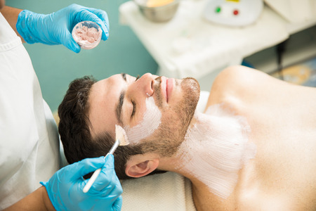Handsome young man getting a facial treatment and an anti-aging mask in a health spa