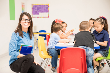 Good looking brunette teaching kindergarten to a group of students and looking happy Archivio Fotografico