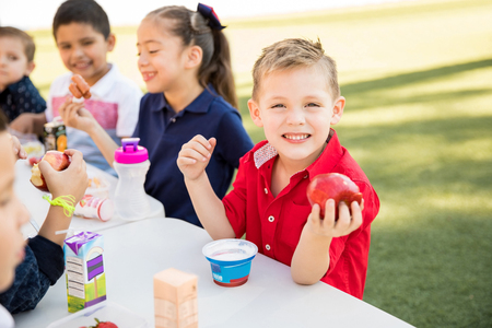 Handsome Caucasian preschooler enjoying his lunch with some of his friends at school and smiling Banque d'images