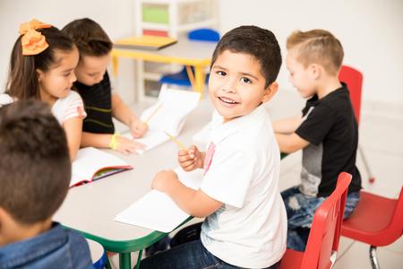 Portrait of a Latin preschool pupil working on a writing assigment and enjoying school Foto de archivo