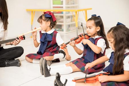 Ładne latynoski w klasie przedszkolnej uczą się muzyki ze swoim nauczycielem