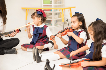 Pretty Latin girls in a preschool class learning some music with their teacher Foto de archivo