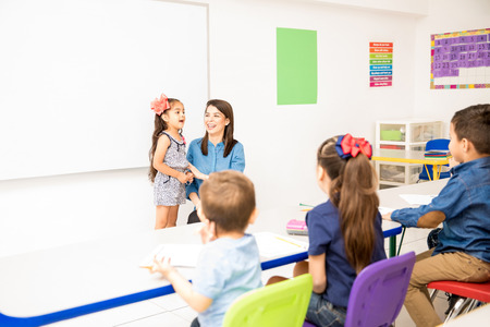 Beautiful little girl participating in class and reciting a poem in a preschool classroom Stockfoto