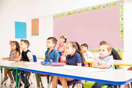 Group of preschool pupils paying attention to their teacher and looking interested in a classroom