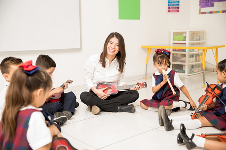 Portrait of an attractive Hispanic brunette teaching music to a group of preschool pupils