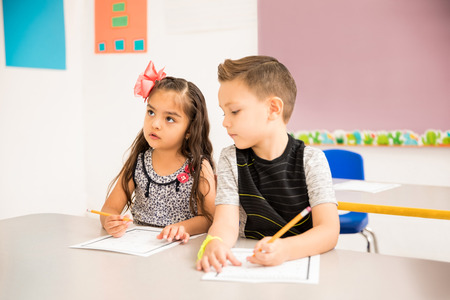 Good looking little kid trying to cheat on a math assigment in a preschool classroom Stock Photo