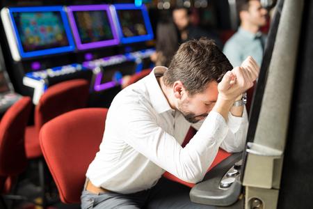Unglücklicher junger Mann, der traurig und gestresst sich fühlt, nachdem er sein Geld verloren hat, Schlitze in einem Kasino spielend Standard-Bild