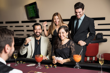 Beautiful young woman looking excited and celebrating with her friends a winning hand at a poker game in a casino