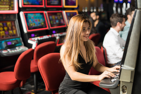 Pretty young woman having a good time playing slots in a casino. With some copy space