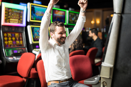 Good looking man looking happy and excited about hitting the jackpot in a slot machine at a casino