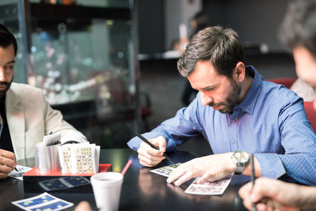 Young man with a beard concentrating on his numbers while playing casino lottery Stock Photo